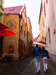 傘を持って通りを歩いくカップルの写真・画像素材[930137]