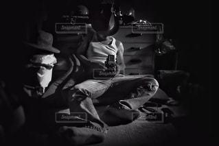 暗い部屋で座っている男の写真・画像素材[930663]