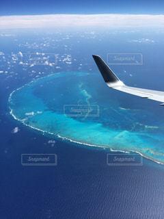 ハワイ旅行の帰りの飛行機。機長さんが普段見ることのできない(政府調査の人以外立ち入りも禁止)世界的にもめずらしく、美しい珊瑚礁の島を見せてくれた。撮っていた時は、感動して声すら出せなかった。ただただ美しかった。これがthe自然の素晴らしさ。の写真・画像素材[931344]