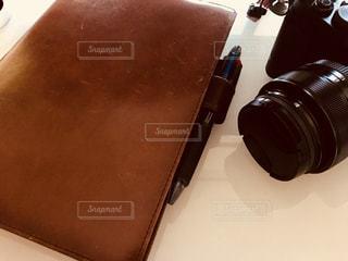 テーブルの上に手帳とカメラの写真・画像素材[1118775]