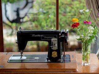 テーブルの上の古いミシンと花瓶の写真・画像素材[1172388]
