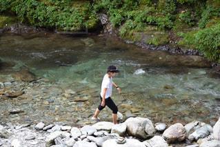 水の横にある岩の上に立っている人の写真・画像素材[741758]