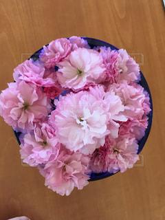木製テーブルの上のピンクの花 - No.1128720