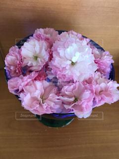 木製テーブルの上のピンクの花の花束の写真・画像素材[1128721]