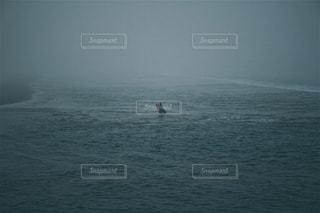 水の体の横に立っている人の写真・画像素材[934295]