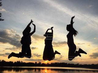 夕陽をバックにジャンプの写真・画像素材[936748]