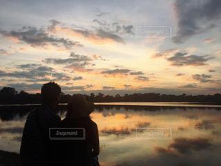 夫婦で眺める夕陽の写真・画像素材[936749]