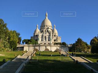 大規模な石造りの建物、バック グラウンドでパリのサクレ ・ クール寺院と教会の前の芝生での写真・画像素材[1727471]
