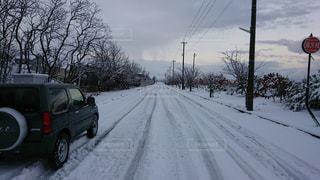 雪に覆われた道の端に停まっている車の写真・画像素材[944598]