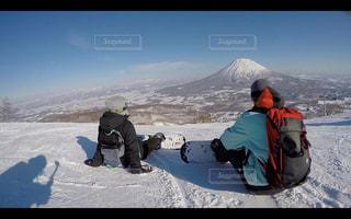 煙る山頂の雪をスノーボードに乗る男の写真・画像素材[1219795]