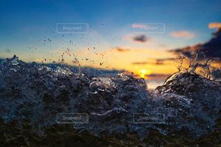 煙る山頂の雪の上を飛ぶ鳥の群れの写真・画像素材[952674]