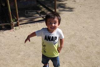 土の中に立っている小さな男の子の写真・画像素材[941270]