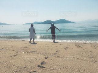 海の横にあるビーチの上を歩く男 - No.1157403