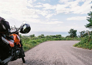未舗装の道路をバイクに乗る男の写真・画像素材[1202309]