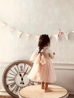 時計の前に立っている女の子の写真・画像素材[944244]