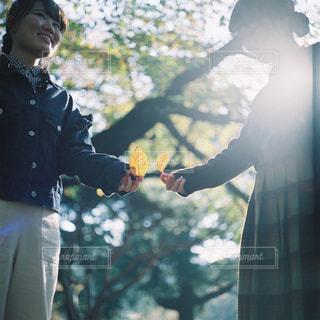 木の隣に立っている男の写真・画像素材[945787]
