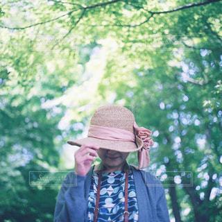 木の隣に立っている男の写真・画像素材[946728]