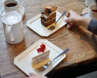 木製のテーブルの上にコーヒー カップとケーキの写真・画像素材[946564]