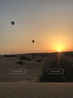 砂漠で気球と朝陽を眺める時間の写真・画像素材[2292711]