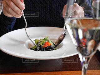 食品のプレートをテーブルに座っている女性の写真・画像素材[949751]