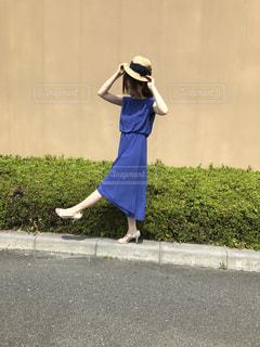 青いワンピースを着て麦わら帽子を持った女の人の写真・画像素材[948700]
