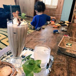 カフェの冷たい飲み物と車のオモチャで遊ぶ男の子の写真・画像素材[948706]