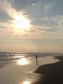 水の体の横にビーチに沈む夕日 - No.949341