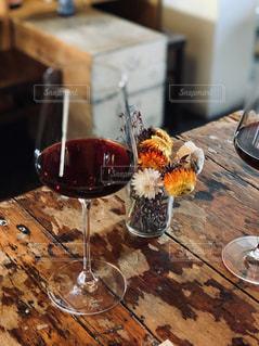 木製テーブルの上に座っているグラスワインの写真・画像素材[2083487]