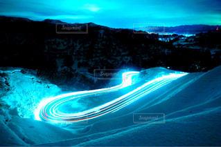 煙る山頂の雪を走る車の写真・画像素材[952171]