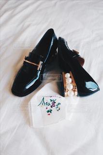 ベッドに横になっている白い靴のペアの写真・画像素材[951723]