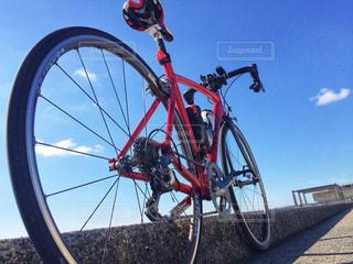 青空に赤いロードバイクの写真・画像素材[981749]
