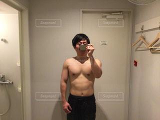 鏡の前で写真を撮っている筋トレ後の男性 - No.952427