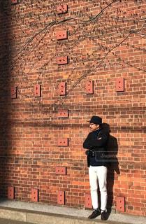 レンガ壁の前に立っている男の写真・画像素材[954720]