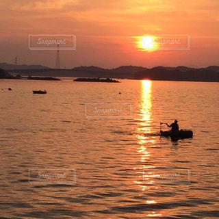 背景の夕日と水の体中の小型船の写真・画像素材[954777]