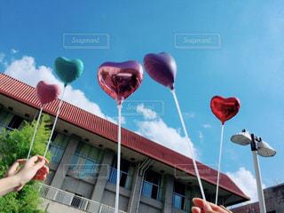 建物の前に赤い傘を持っている手の写真・画像素材[771908]