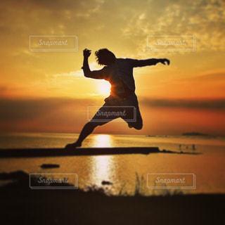 夕日をバックに飛ぶ男の写真・画像素材[955318]