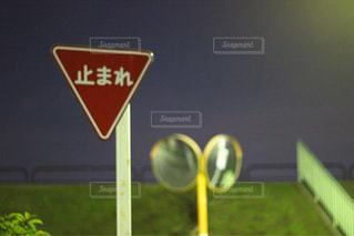 草の上に座って赤い停止記号 - No.957079