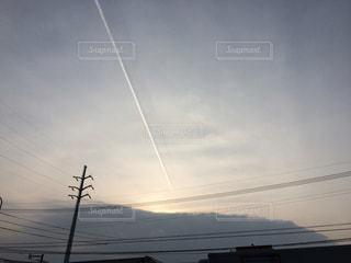冬空の夕日と、飛行機雲の写真・画像素材[958210]