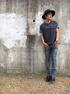 レンガ壁の前に立っている男の写真・画像素材[959228]