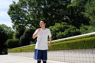 フェンスの横に立っている人の写真・画像素材[1396451]