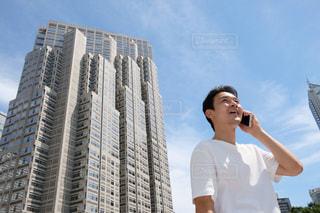 背の高い建物の前に立っている人の写真・画像素材[1396453]