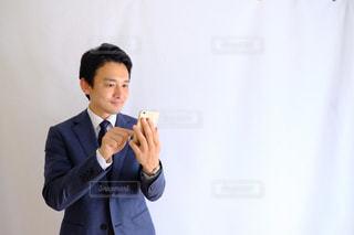 スーツと携帯電話で話しているネクタイを身に着けている男の写真・画像素材[1462640]
