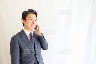 身に着けているスーツとネクタイは、携帯電話で話す人の写真・画像素材[1462646]