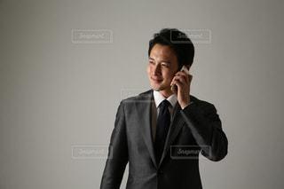 スーツと携帯電話で話しているネクタイを身に着けている男の写真・画像素材[1634725]