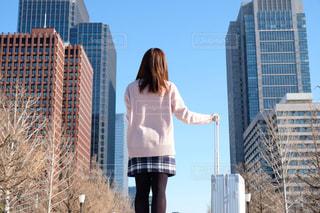 背の高いビルの前に立っている女の子の写真・画像素材[1707396]