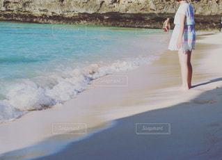 水の体の近くのビーチに立っている女性の写真・画像素材[960385]