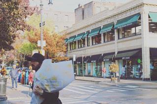 花束を抱えて道を歩いている人の写真・画像素材[960392]