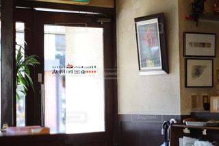 窓の前のテーブルに座っている人の写真・画像素材[1059824]