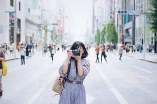カメラを構えている通りに立っている女性の写真・画像素材[2440451]
