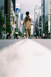 道路の脇にスケートボードに乗っている男の写真・画像素材[2440462]